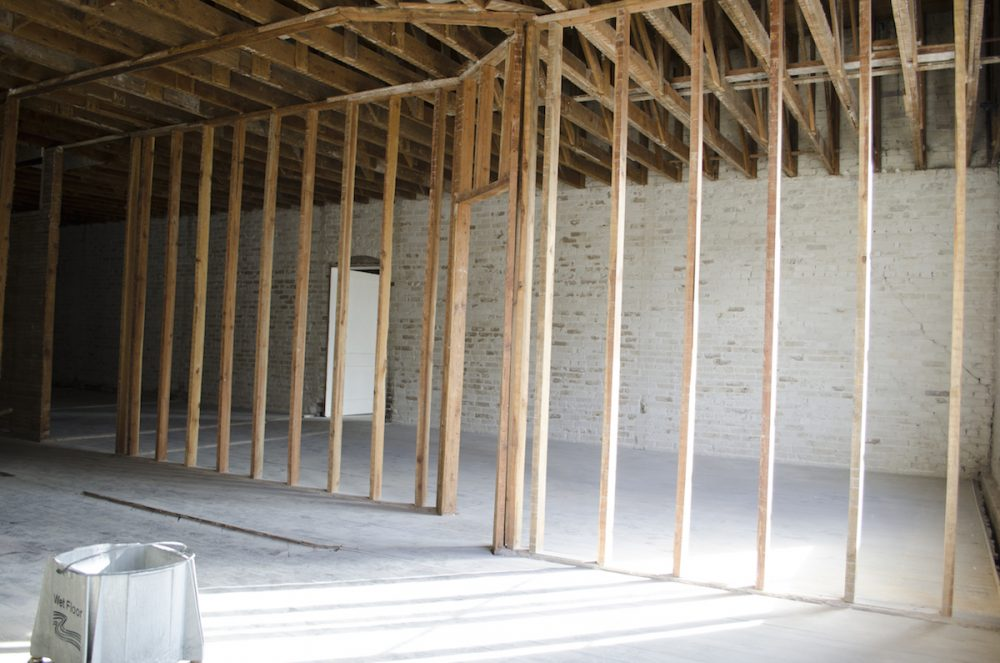 Original 1920s brick walls and hardwood floors are being fully restored.